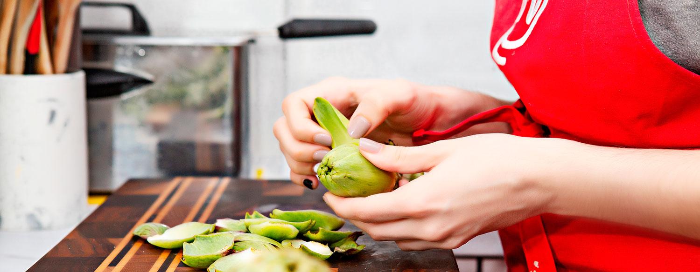 mujer en cocina lista para cocinar alcachofas